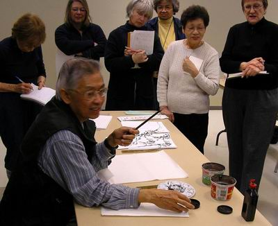 Charles Leung discusses brushes and paper with workshop participants