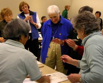 Roslyn discusses painting with several workshop participants