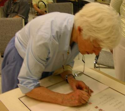 Ann Abraham signs Sumi-e Artists of Canada scroll with her seal